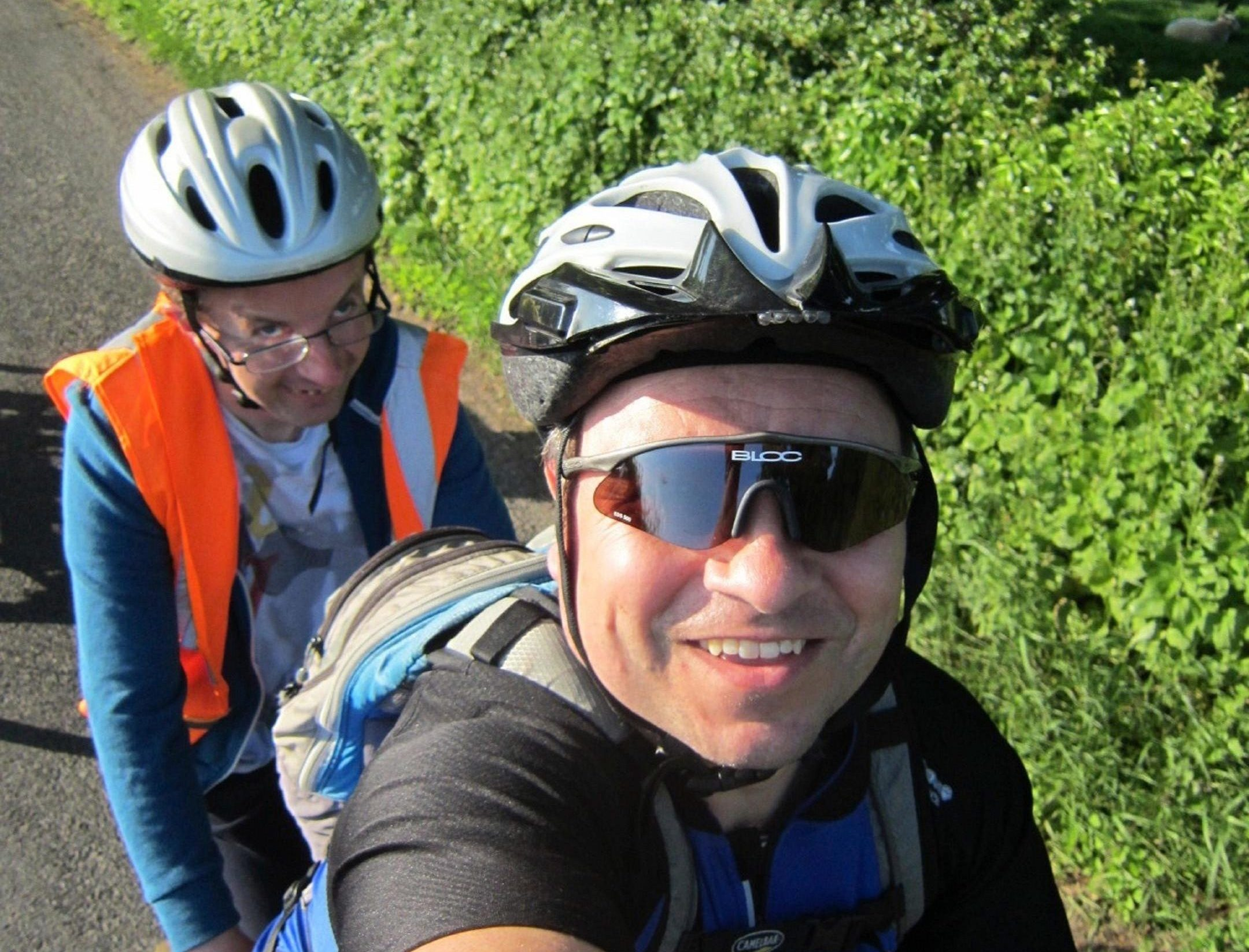 A close up of two people on a tandem riding by a hedgerow.