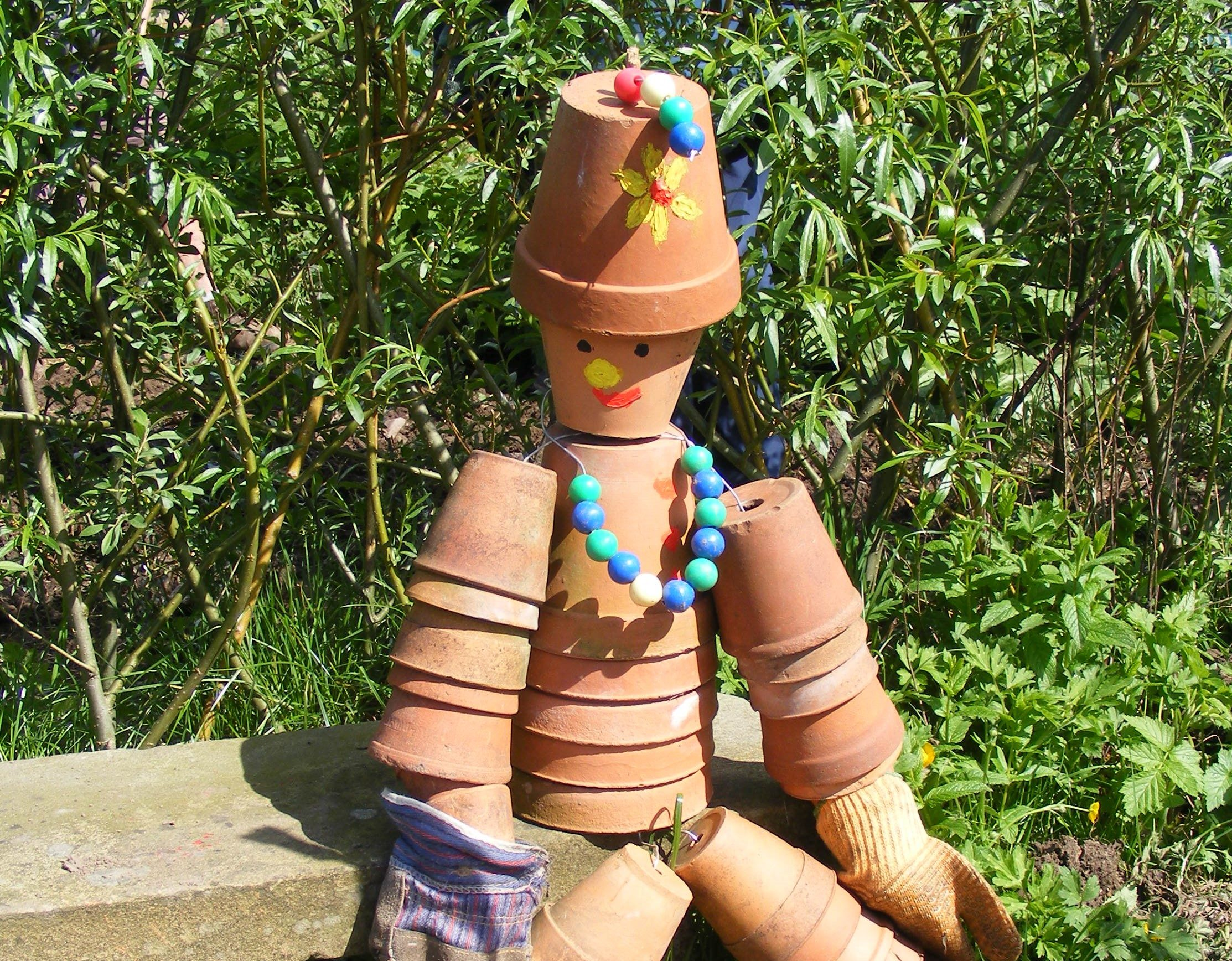 A figure made out of terracotta pots sitting on a bench down the allotment.