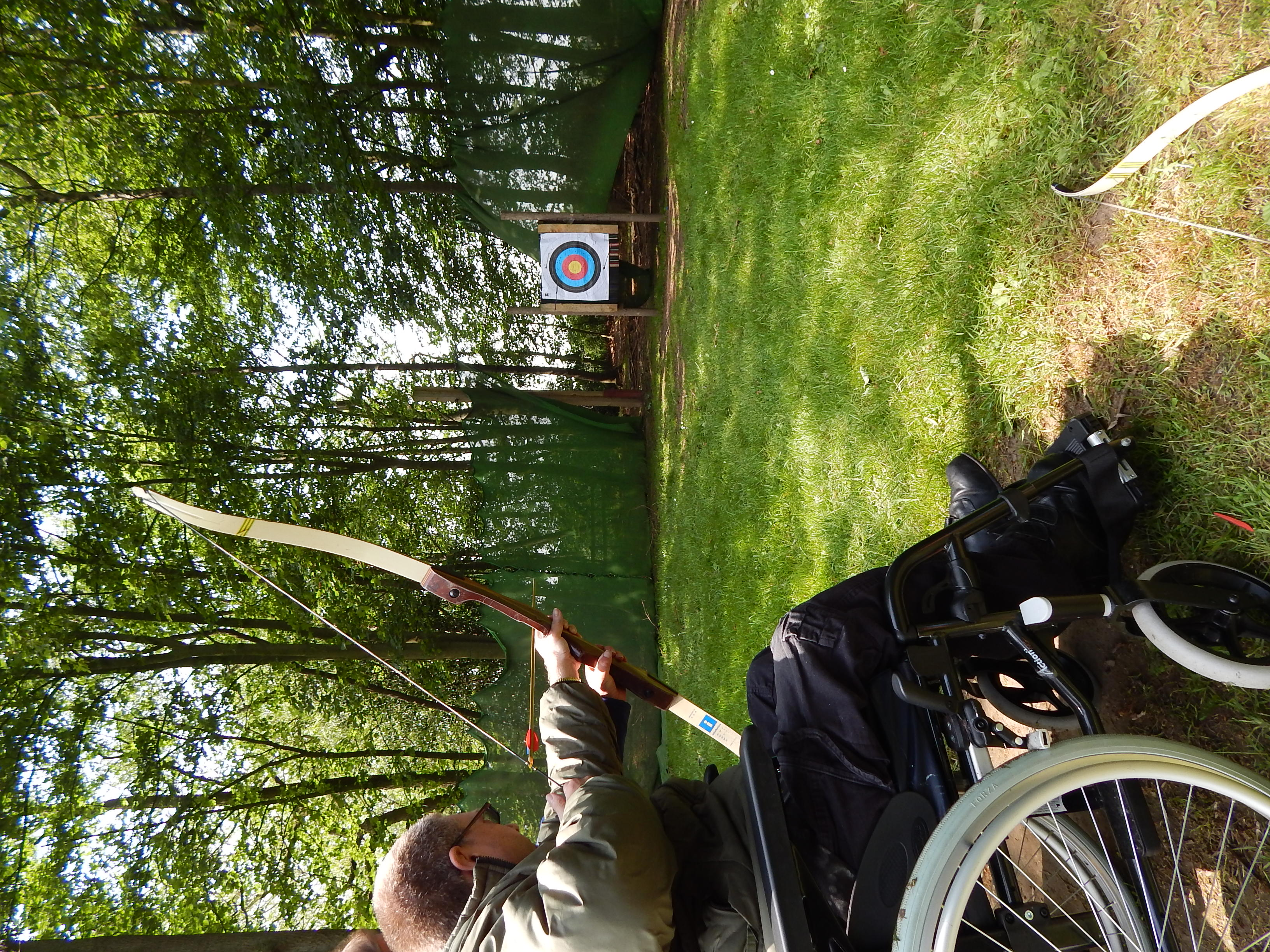 A man in a wheelchair doing archery on grass with woods behind.