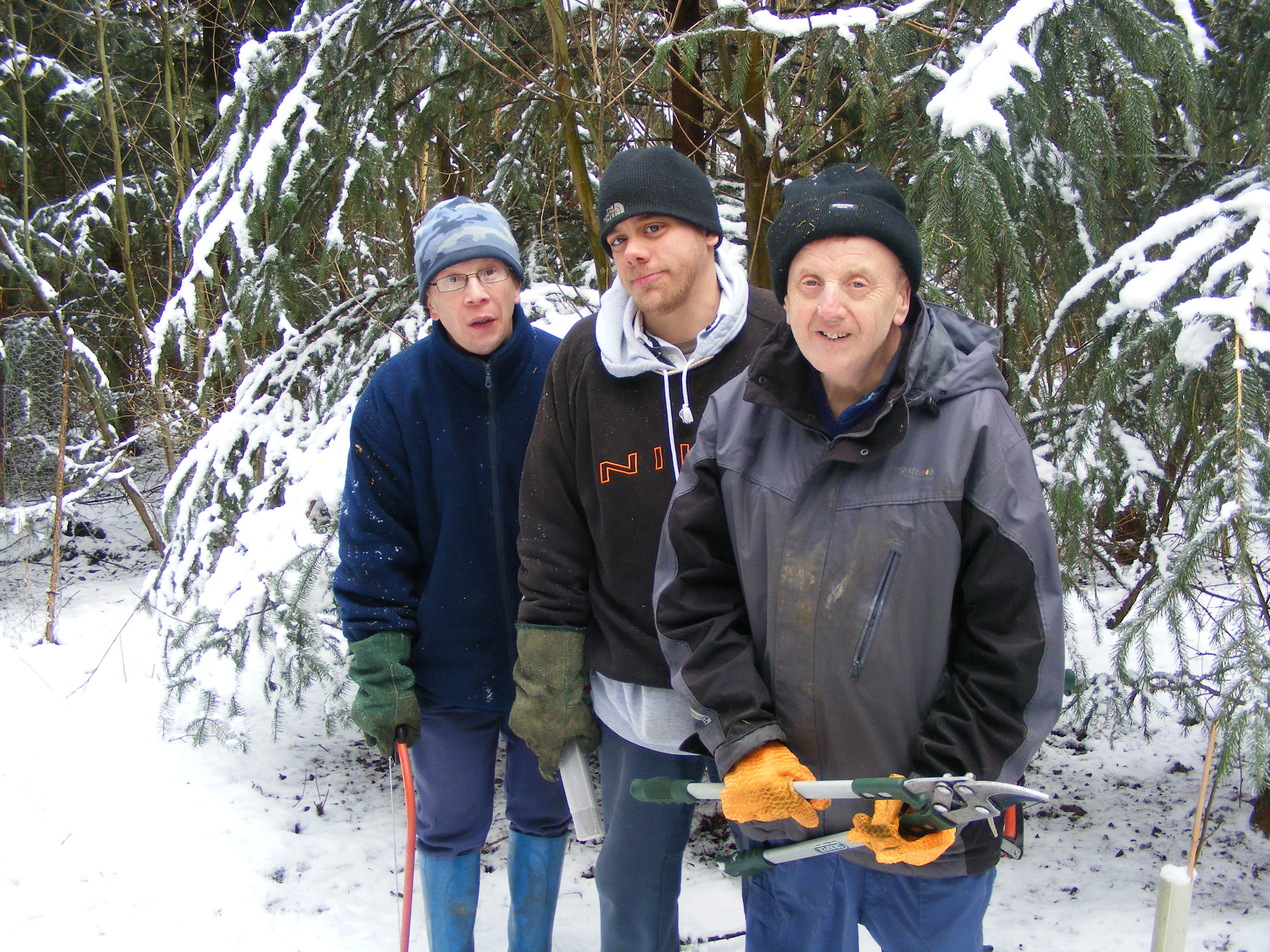 Three people holding loppers and bowsaws in a snowy woodland.