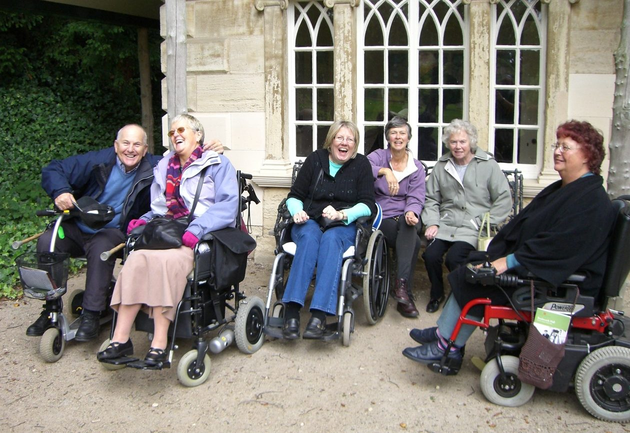 Four people in wheelchairs laughing outside an old building.