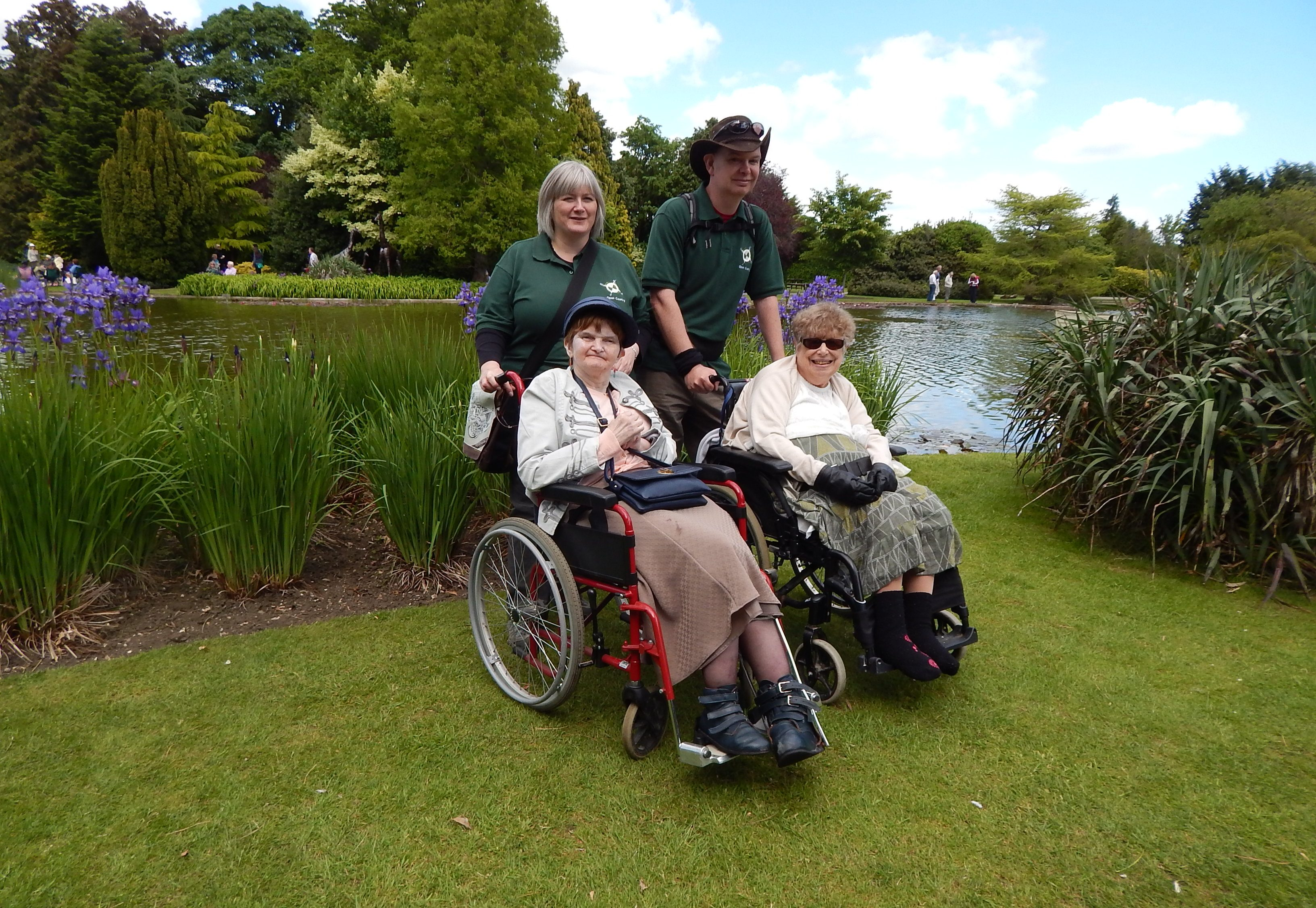 A man and a woman standing on grass behind two women in wheelchairs. There is a lake and trees in the background.
