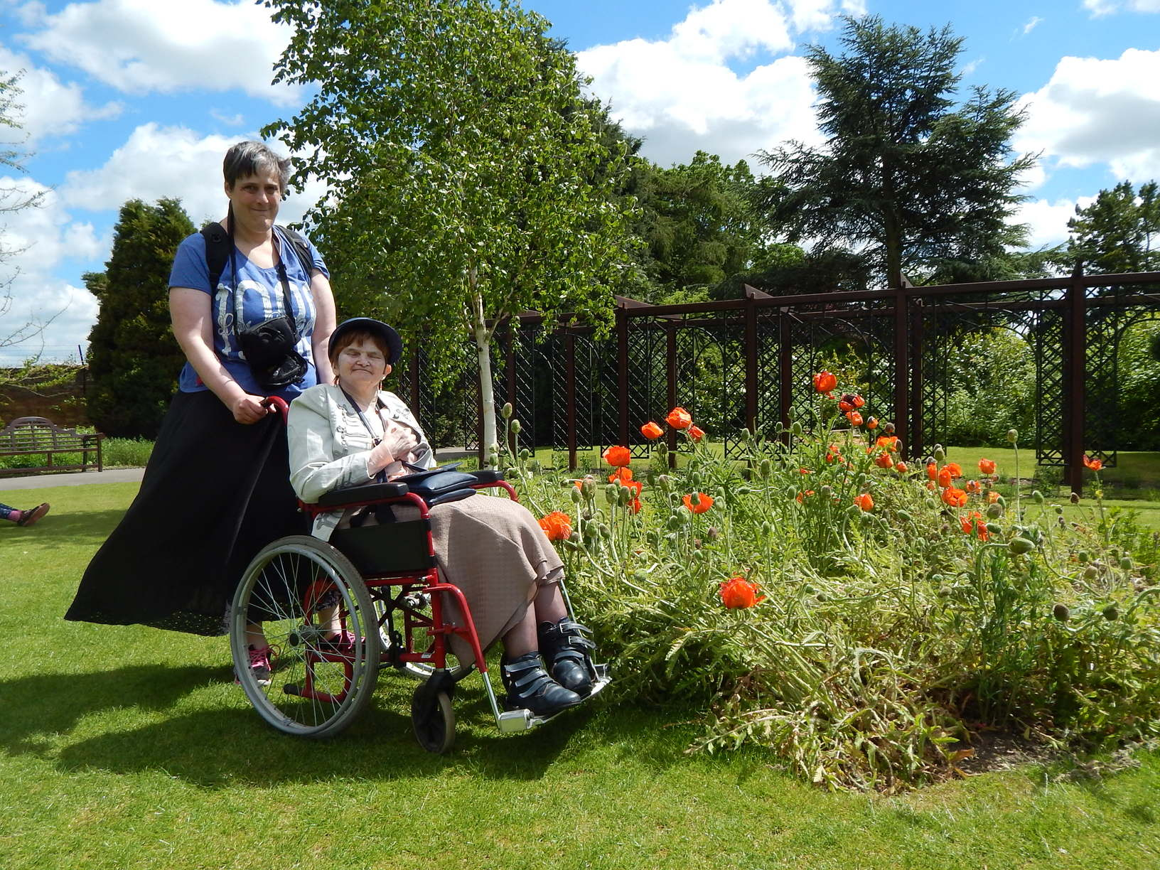 Two people, one in a wheelchair, enjoying a leisurely walk through a pretty garden.