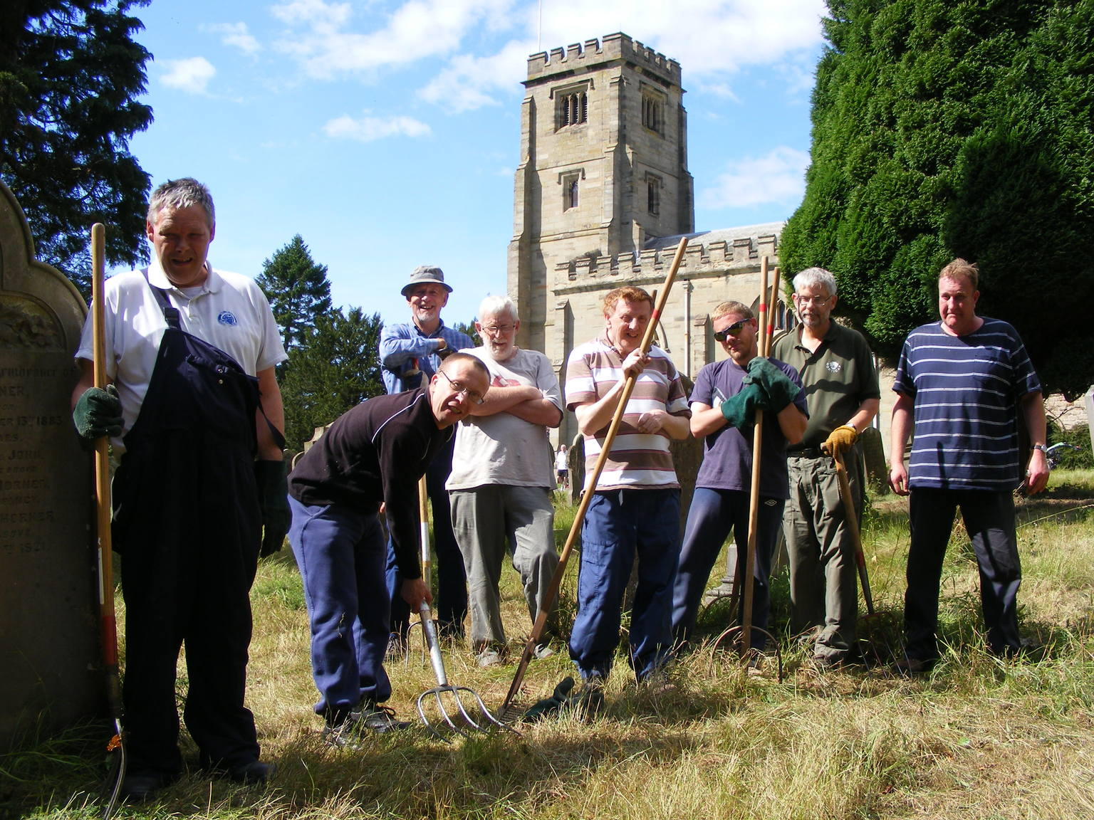 The group in a churchyard posing with tools after raking up following a meadow cut.