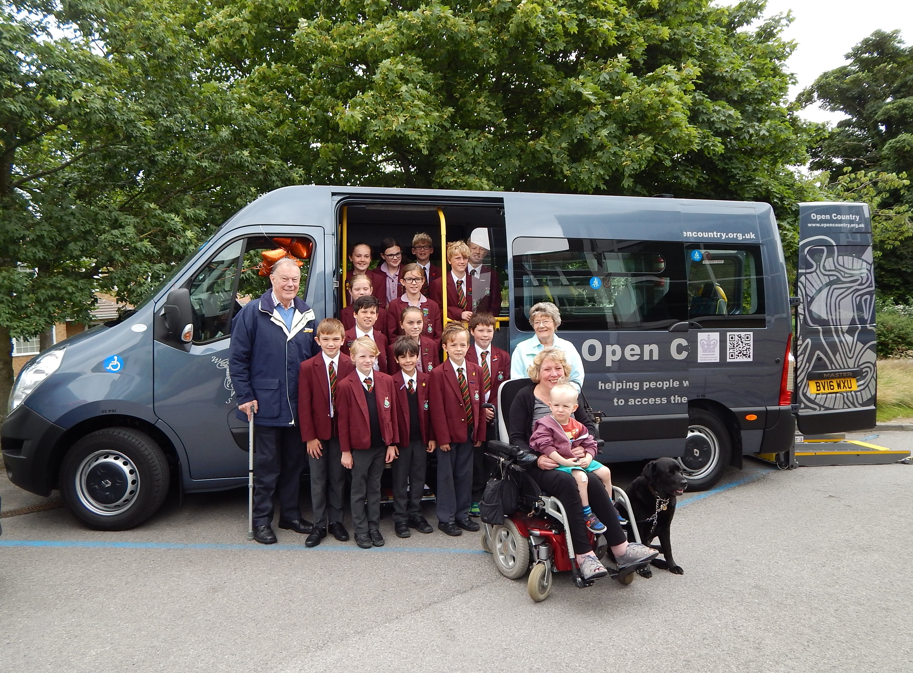 A group of school children standing next to a minibus with a lady in a wheelchair and her assistance dog
