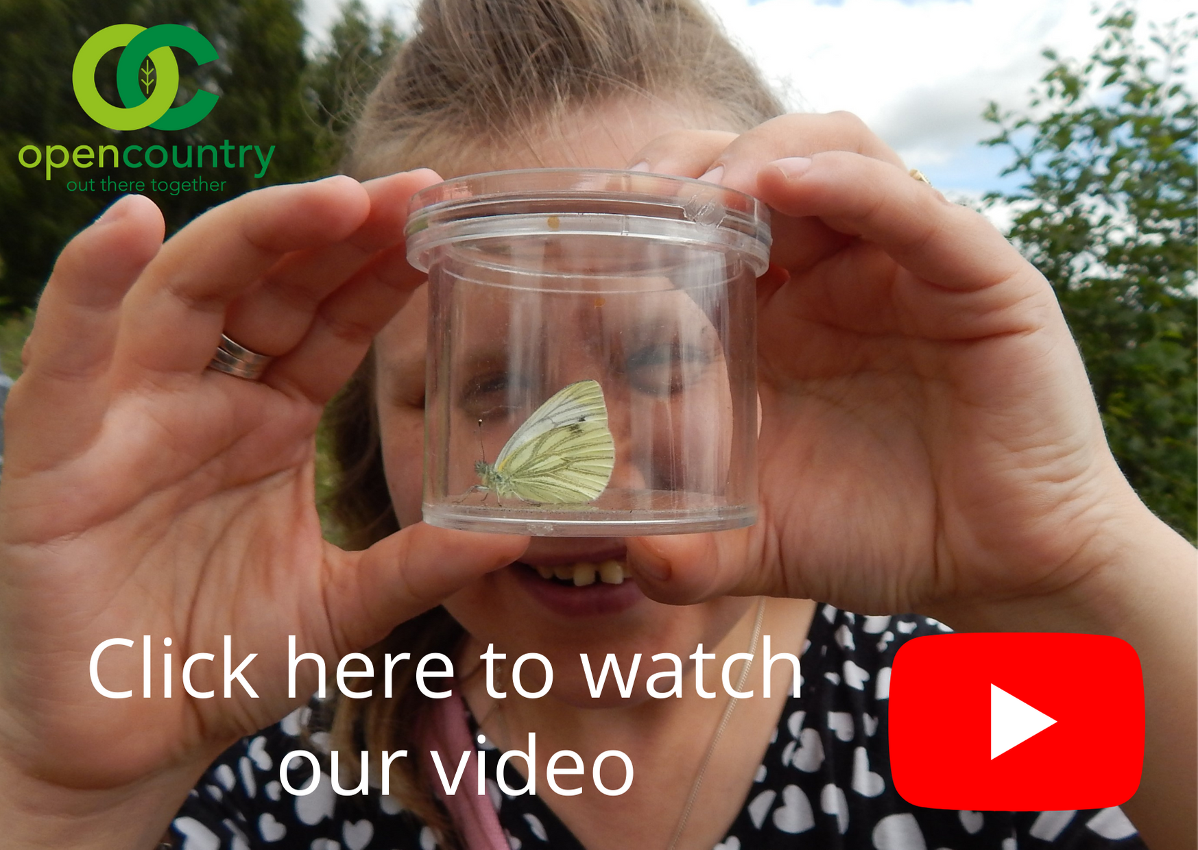An Open Country member examines a butterfly up close in a specimen pot