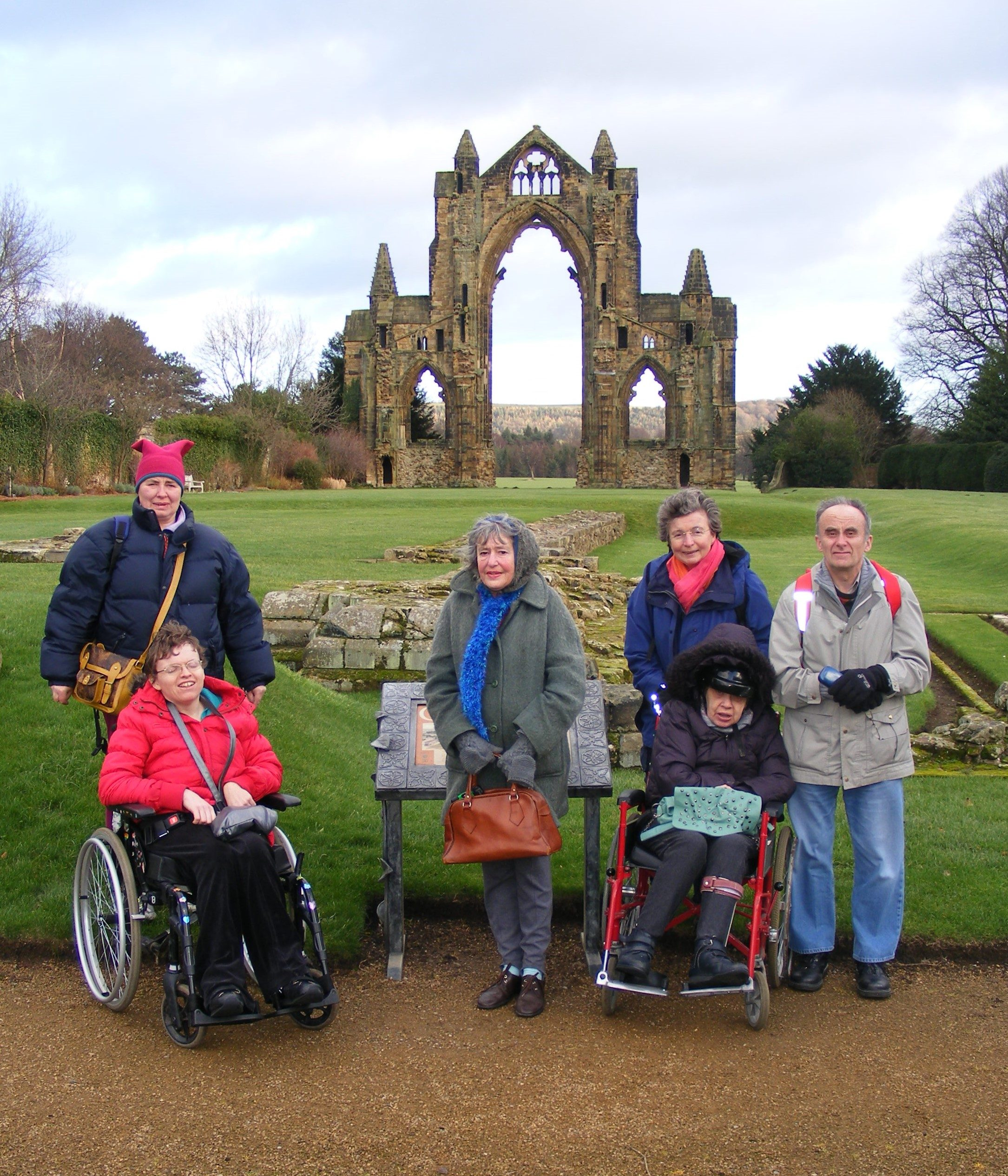 A group, some standing, some in wheelchairs, outside, with Guisborough Priory in the background.