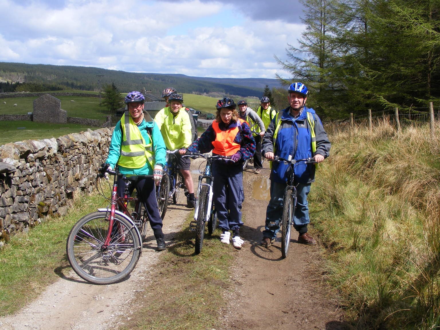 People on bikes on a bridleway next to a dry stone wall, with hills in the background.