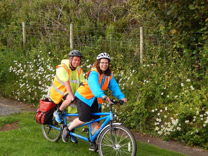 A woman piloting a tandem with a man on the back, riding down a country lane.