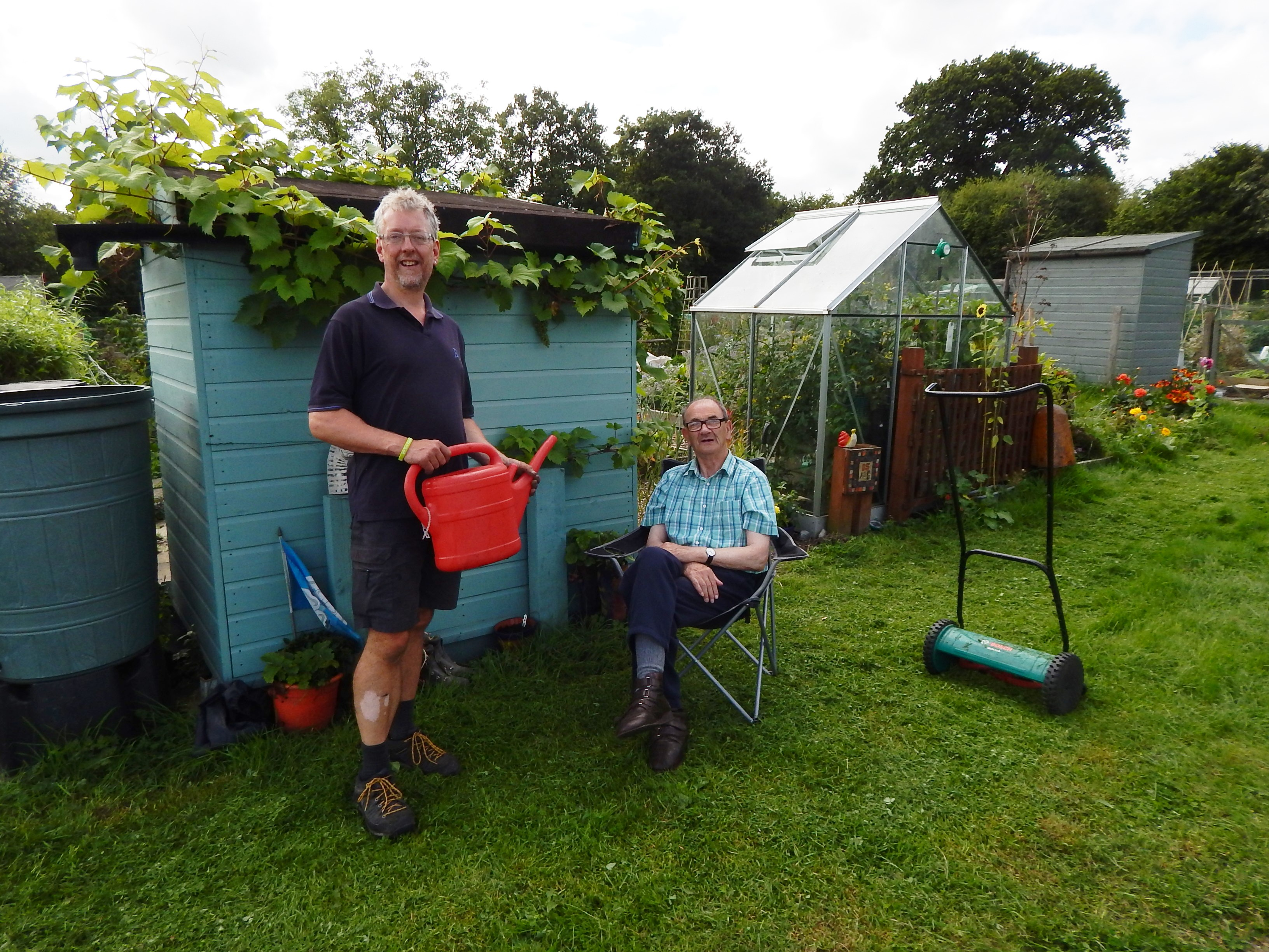 Two men at an allotment by a shed; one is sitting down, the other is standing holding a watering can.