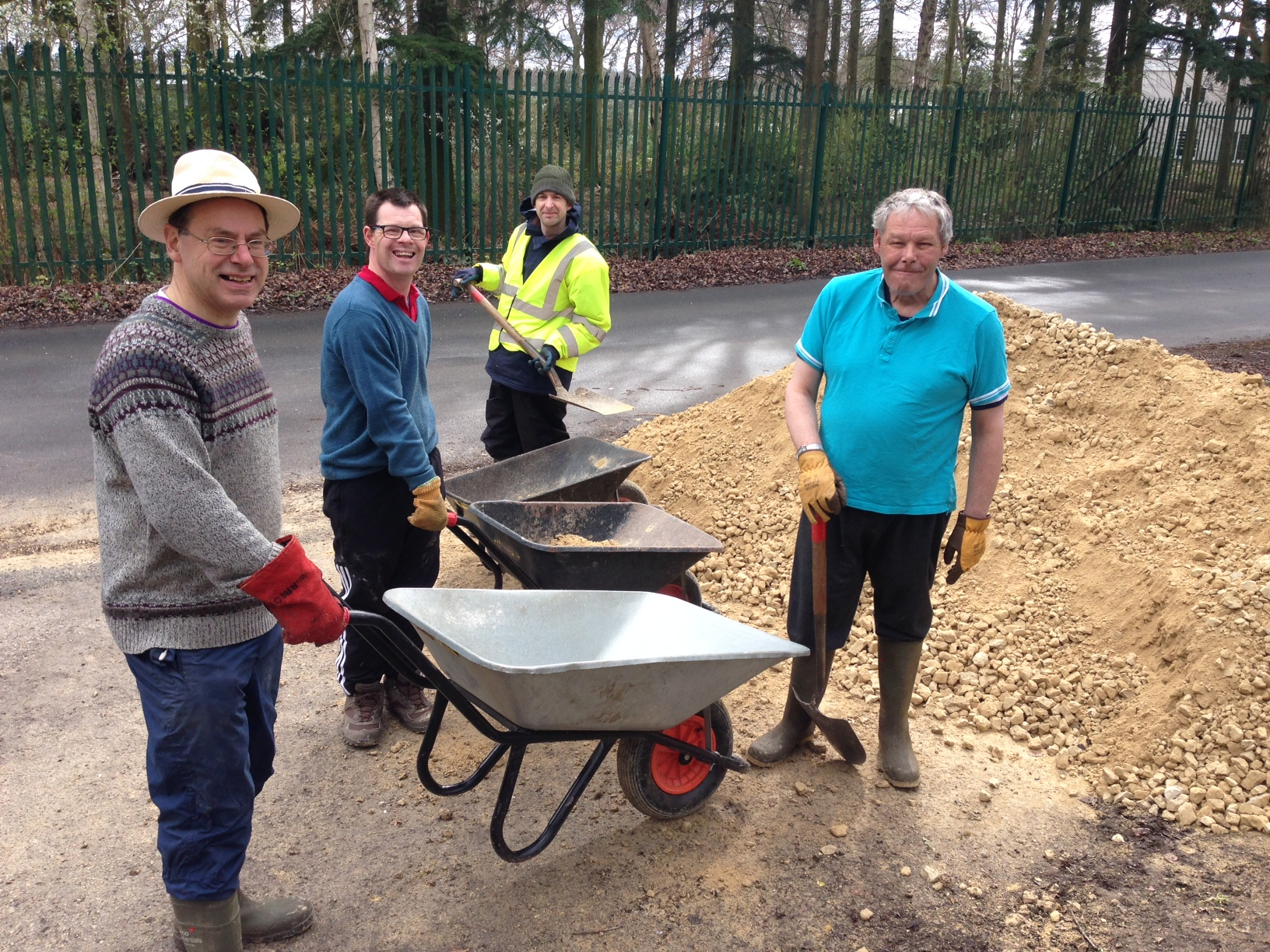 The group doing path work, standing next to wheelbarrows with shovels.