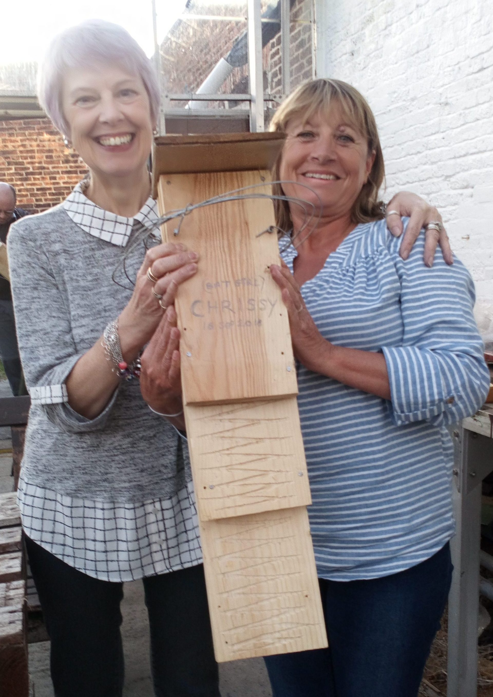 Two women holding a large bat box that they have made