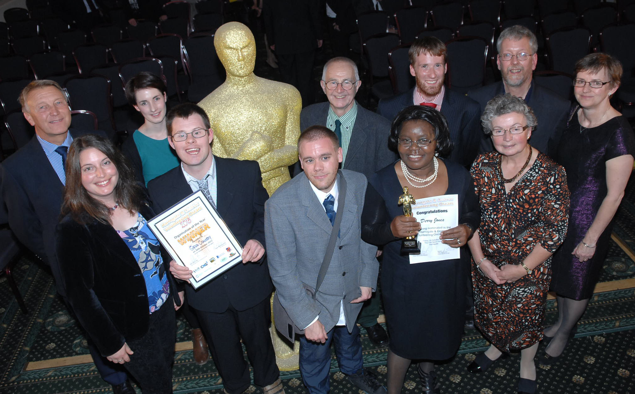 A group of people smartly dressed holding certificates and awards.