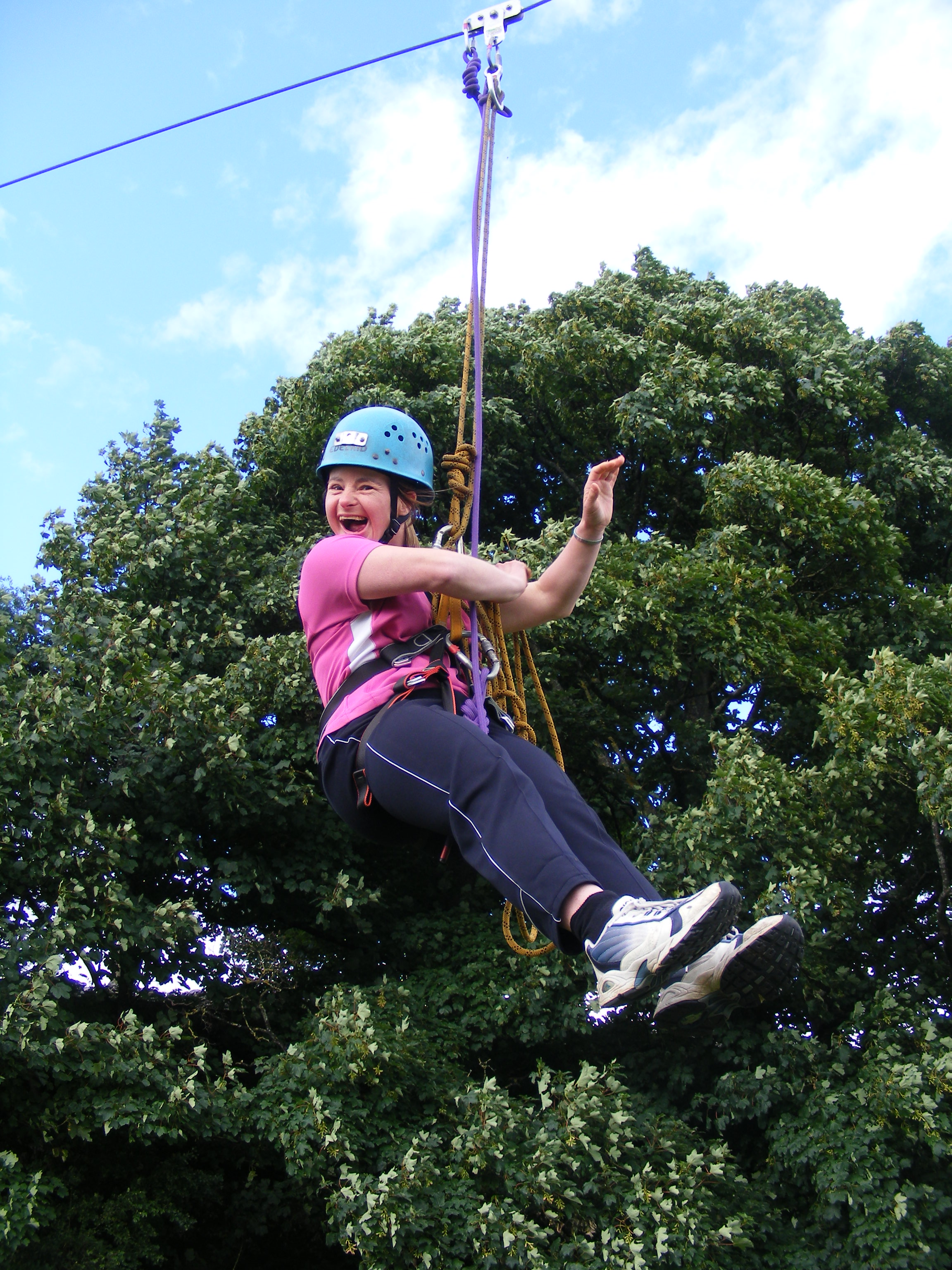 A woman on a zip wire with trees behind