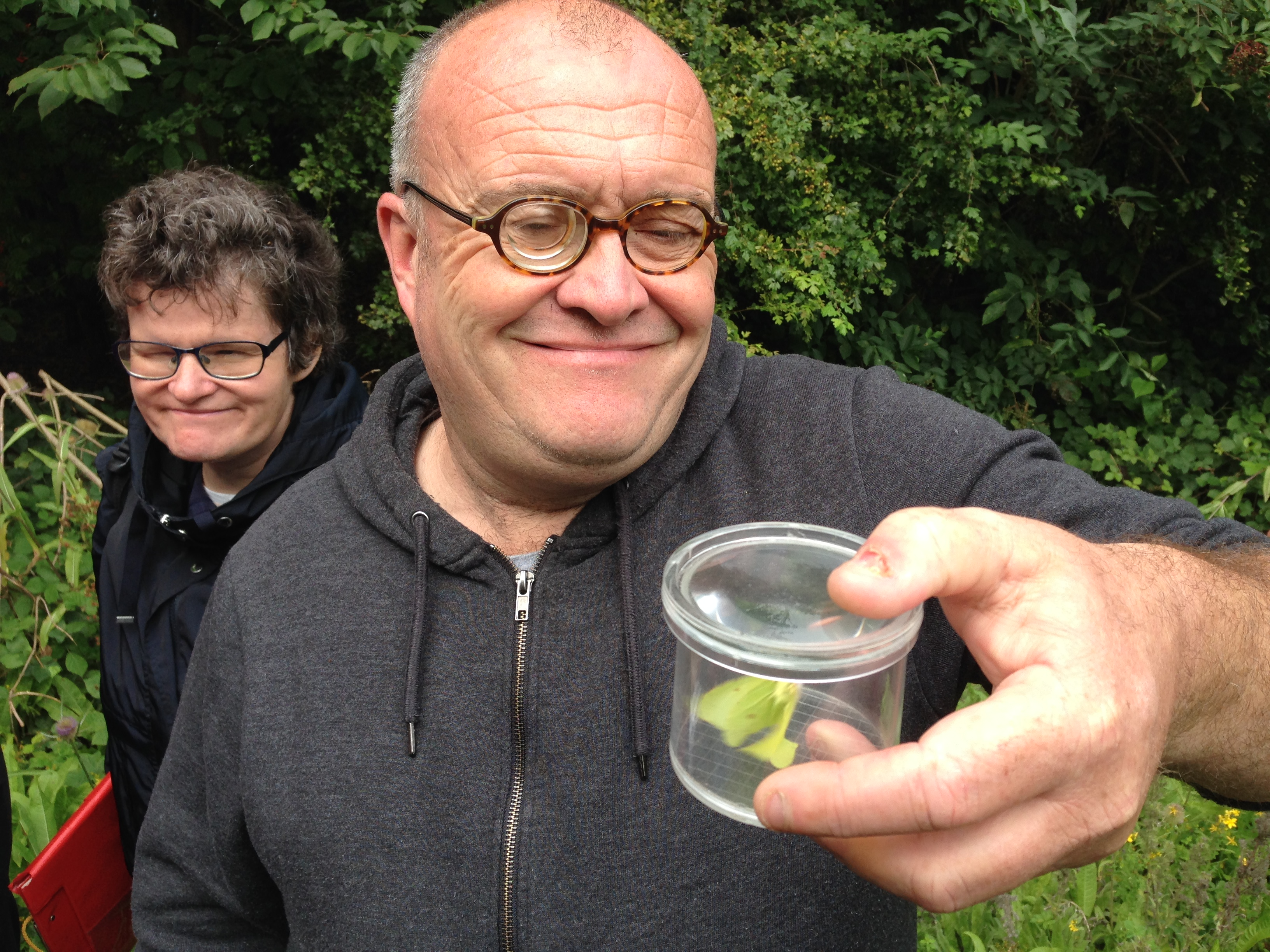 A man smiling and holding a clear container with a butterfly in. A woman is standing behind looking.