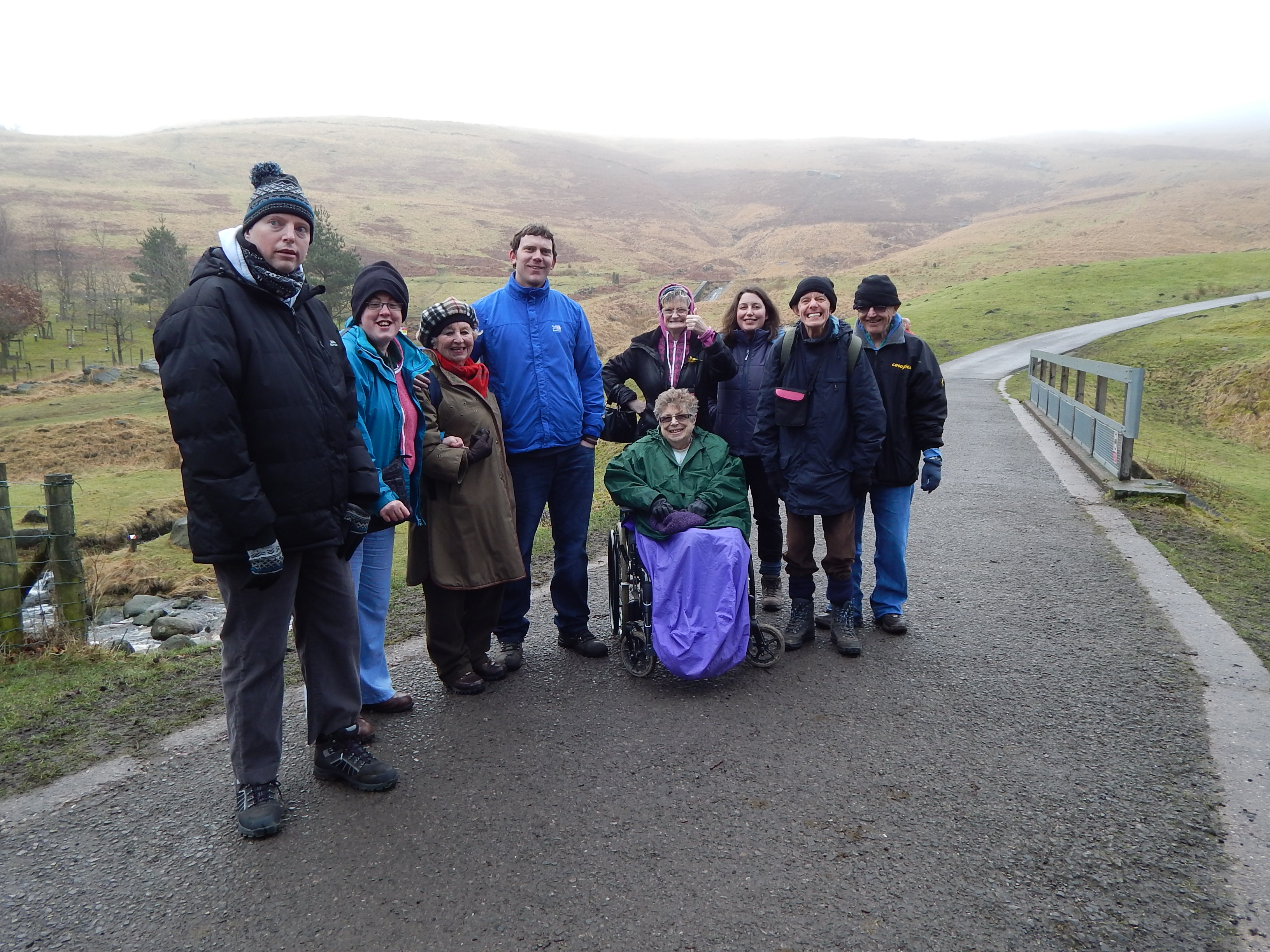 A group of people, one in a wheelchair, on a path with hills and mist behind.