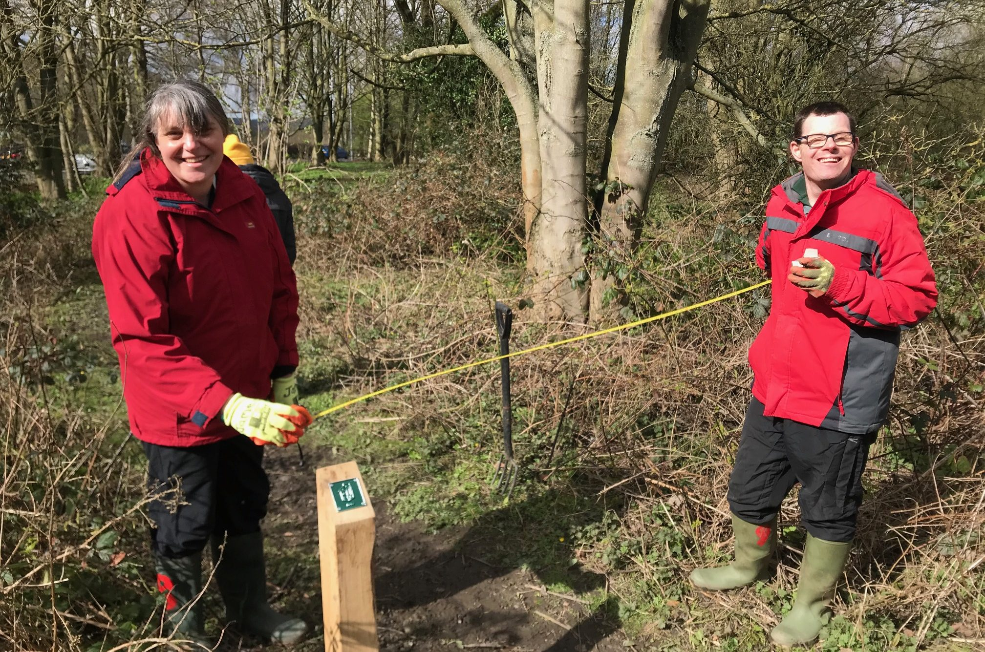 A man and a woman in wellies holding a tape measure next to a nature trail sign post