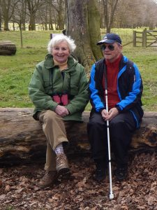 Volunteer Dottie and Mike sitting together on a log