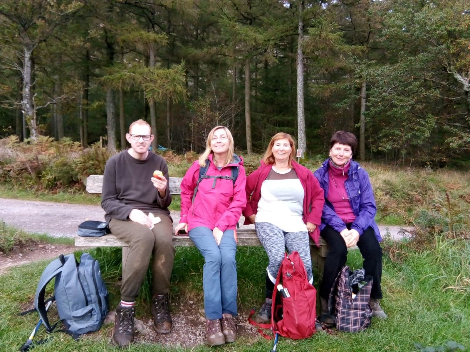 Four people sittong on a bench with woodland behind.