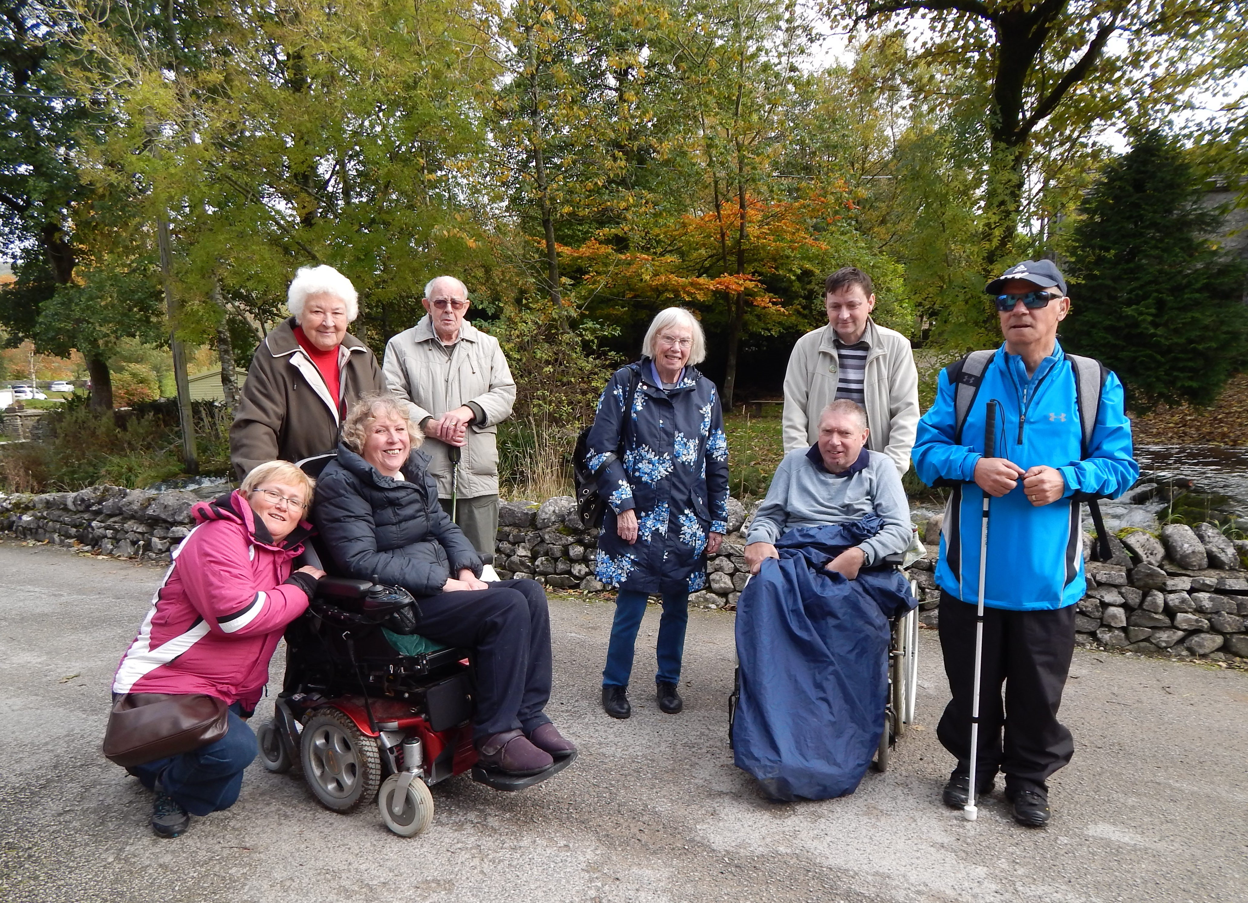 Eight people smiling with autumn trees behind.