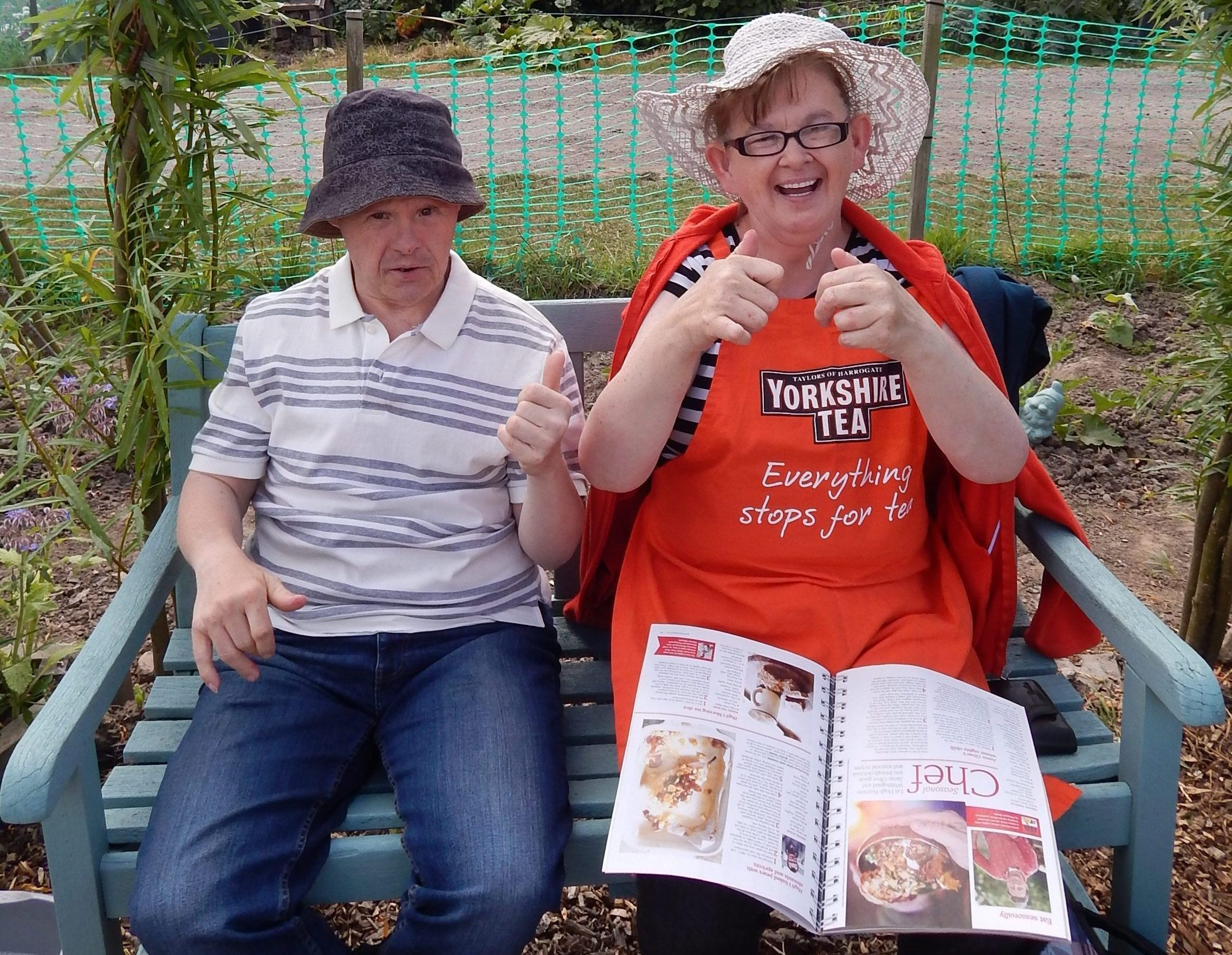 Two people sitting outside under a willow arch, one has a magazine on her lap