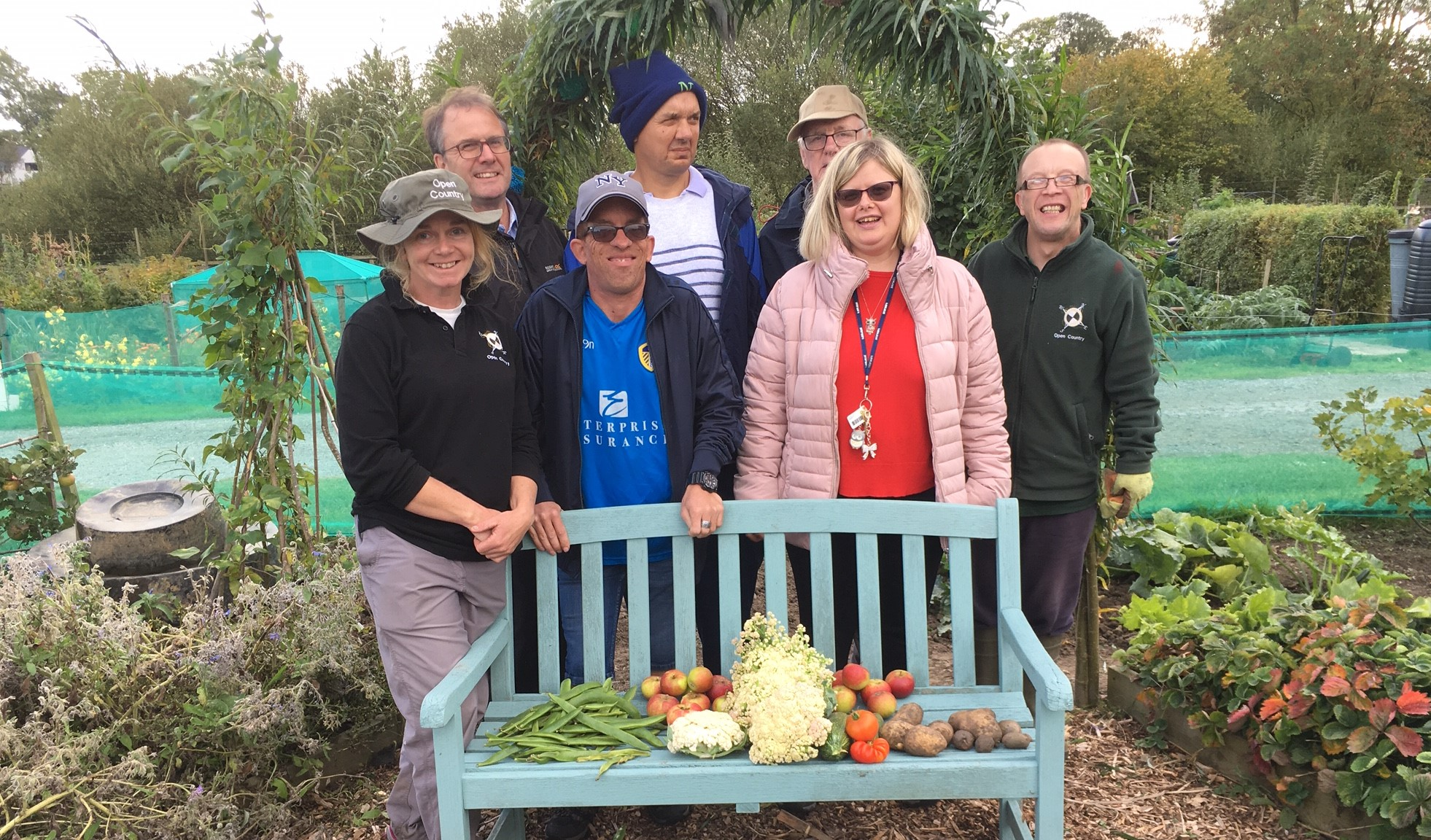 A group of people standing behind a bench with allotment produce on.