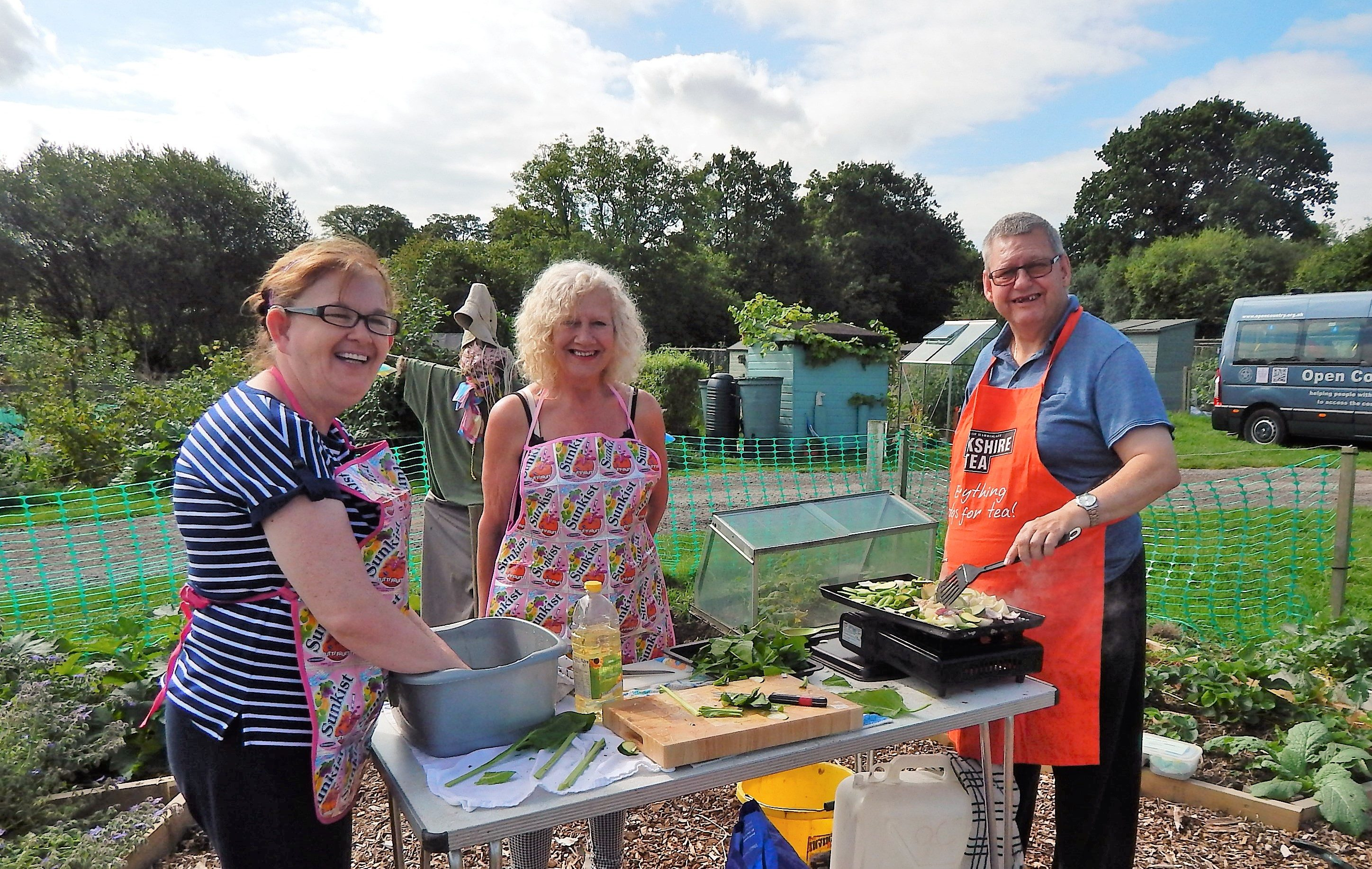 Two women and a man cooking on a table down an allotment.
